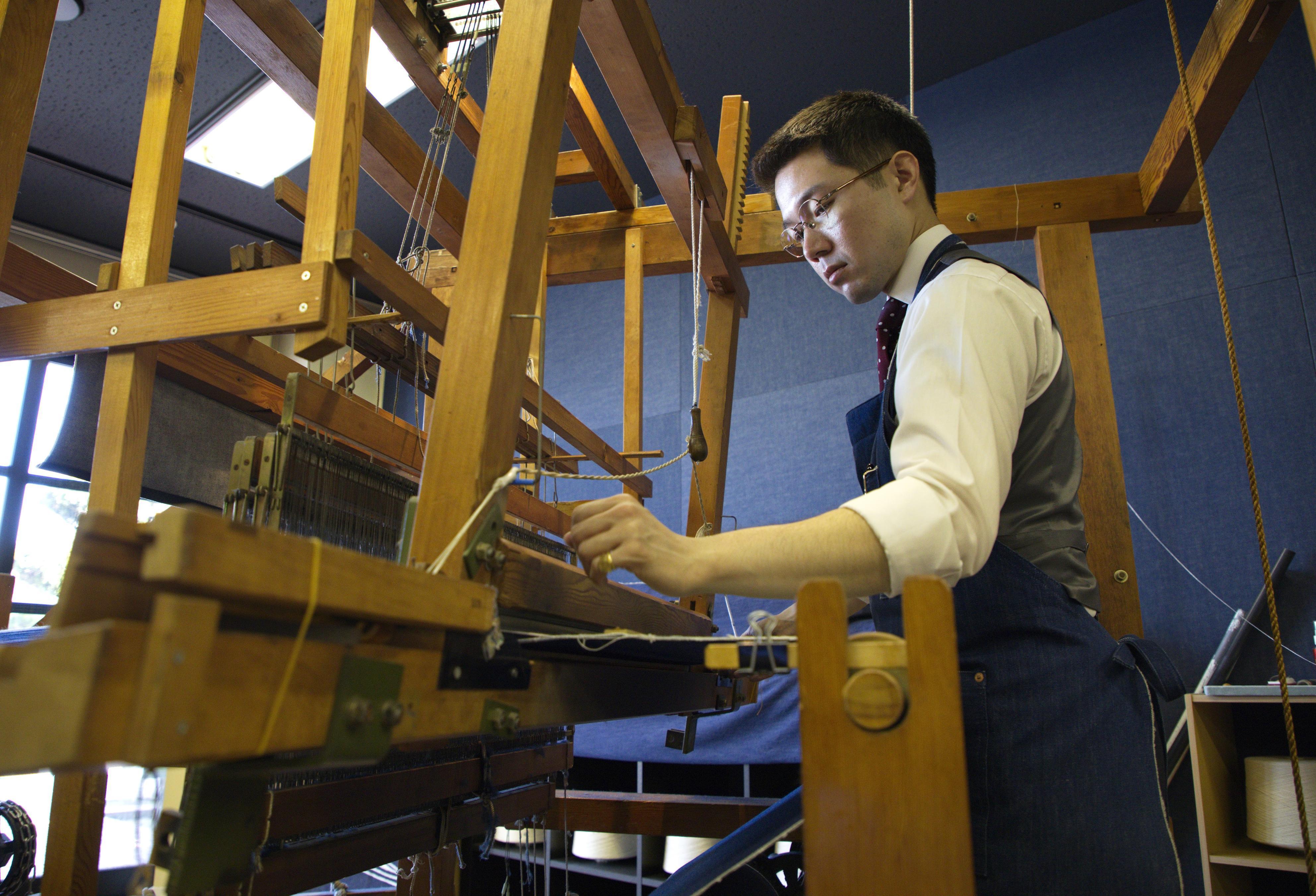 藍で染めた糸を手織りする池田一貴。ゆっくりと時間をかけて仕上げていく=岡山県倉敷市