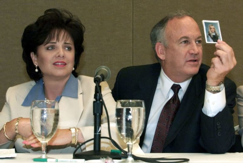 2000年5月24日、米アトランタでの記者会見で、ジョンベネちゃんの写真を示す両親(ロイター=共同)