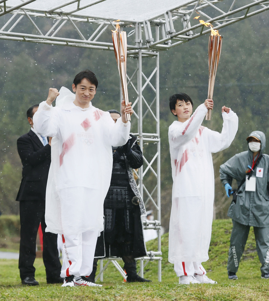 次走者の山本耕史さん(左)に聖火を引き継いだ田内恒樹さん=4日午後、岐阜県関ケ原町