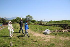 予約不要のワンコインガイドで案内を受ける来訪者(左2人)=南島原市、原城跡