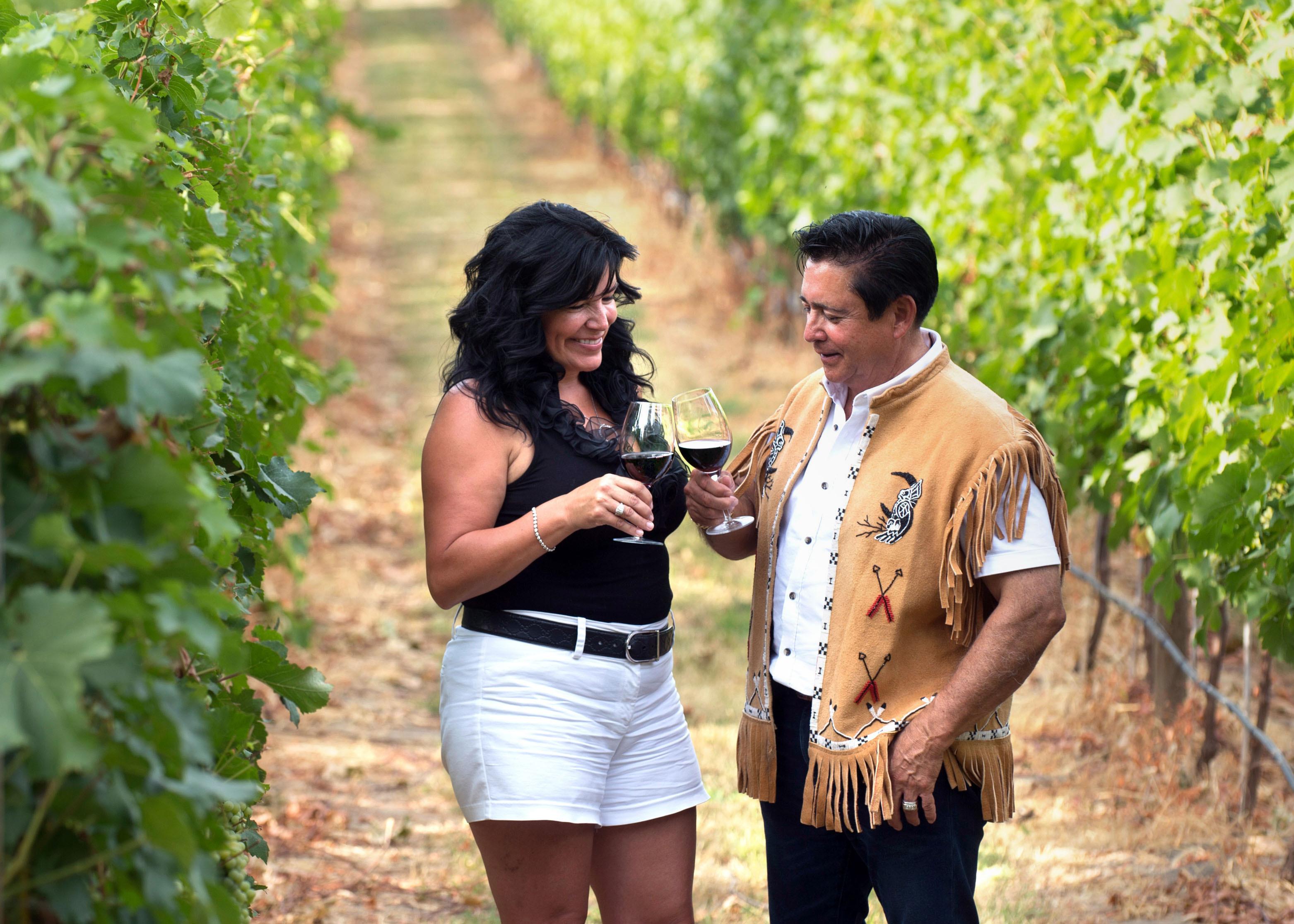 ワイナリーのブドウ畑で乾杯するロバート・ルイー(右)と妻ベニース。先祖から受け継いだ土地でワインづくりに情熱を燃やす=カナダ・ブリティッシュコロンビア州オカナガン地方(撮影・鍋島明子、共同)