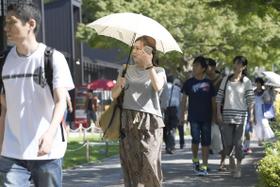 強い日差しの中、日傘を差して歩く女性=15日午後、名古屋市