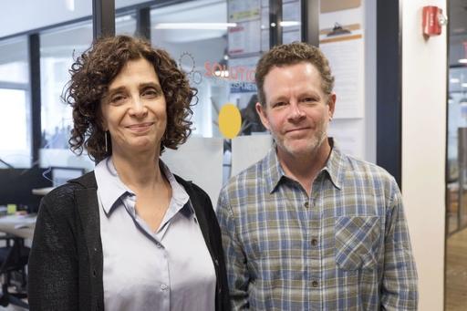 ソリューションズ・ジャーナリズム・ネットワーク共同創設者のティナ・ローゼンバーグ(左)とデービッド・ボロンスティン。ガラスのついたてで仕切られた小さな事務所がひしめく共用オフィスビルの一角に本拠地を置く=19年9月、米ニューヨーク(共同)
