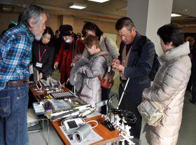 【展示品を手に取って確認する来場者ら=津市桜橋の県社会福祉会館で】