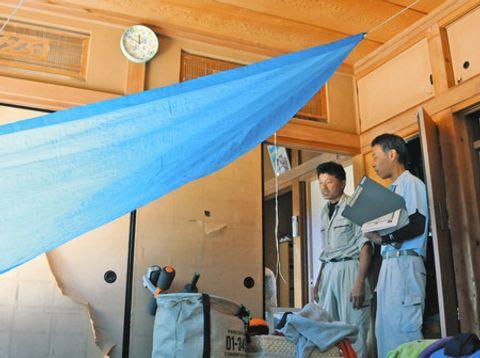 千葉県南房総市内の民家2階で、住人の男性(左)とともに損壊の程度を確認する市職員の小沢一宏さん=山口登史撮影
