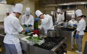 9日の営業を前に、食材を仕込む学生たち=古河市東