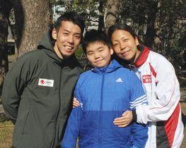 寄り添う(左から)高田裕士選手と諭樹君、千明選手=東京都港区で(神谷円香撮影) 写真