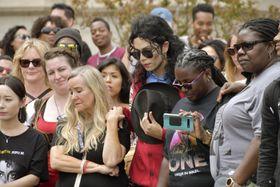 マイケル・ジャクソンさんの墓地前で黙とうをささげるファンら=25日、米カリフォルニア州グレンデール(共同)