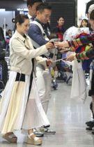 ファンにサインするサッカーW杯日本代表候補の長友と妻で女優の平愛梨さん=22日、成田空港