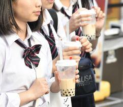 タピオカドリンクを持って歩く学生=東京都渋谷区