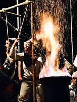 踏みふいごで風を送る参加者。木炭と砂鉄を熱して鉄を作る=13日、深夜