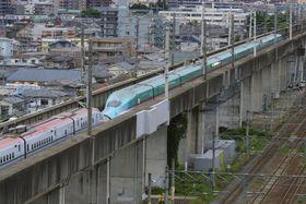 一時的な停電で停止したままの東北新幹線はやぶさ・こまち21号。奥は仙台市街=17日午後