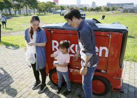 デモンストレーションで、注文した商品を受け取る利用者=19日午後、神奈川県横須賀市のうみかぜ公園