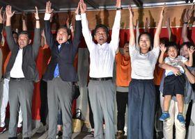 初当選を飾り、万歳する小林栄氏(左から3人目)=4日午後8時38分、結城市新福寺