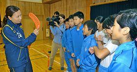 津田志穂さん(左)からスティックの使い方を教わる児童たち