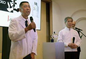 19日、ロンドンの日本大使公邸でのイベントで、「匠の技」を説明するセイコーエプソンの中沢義房さん(左)とサントリースピリッツの鳥井和之さん(共同)