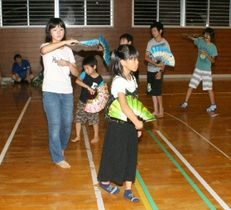 扇子を手に風流踊りの練習に励む子どもら=佐伯市弥生尺間の尺間体育館