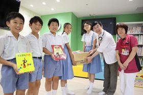 森内教授に図書を手渡す長崎南山小児童会の子どもたち=長崎大学病院