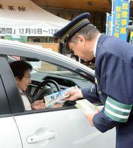 拉致問題の情報提供を呼び掛けるチラシを配る警察官=日置市東市来の江口蓬莱館