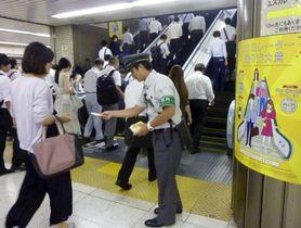 東京駅のエスカレーターを利用する通勤客。駅員が手すりにつかまるよう呼び掛けている。