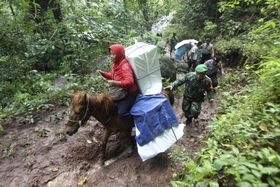 15日、インドネシアの東ジャワ州で、へき地の村に向けて馬で運ばれる投票箱(AP=共同)