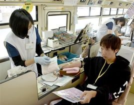 県赤十字血液センターの献血バスで献血する熊本大生=18日、熊本市中央区