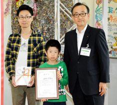 30万人目の認定証を手にする悠真君(中央)。左は父忠嘉さん、右は渡辺副所長