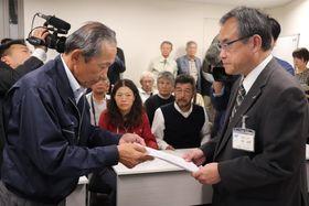 県土木部の天野俊男次長に抗議文を手渡す炭谷氏(左)=県庁