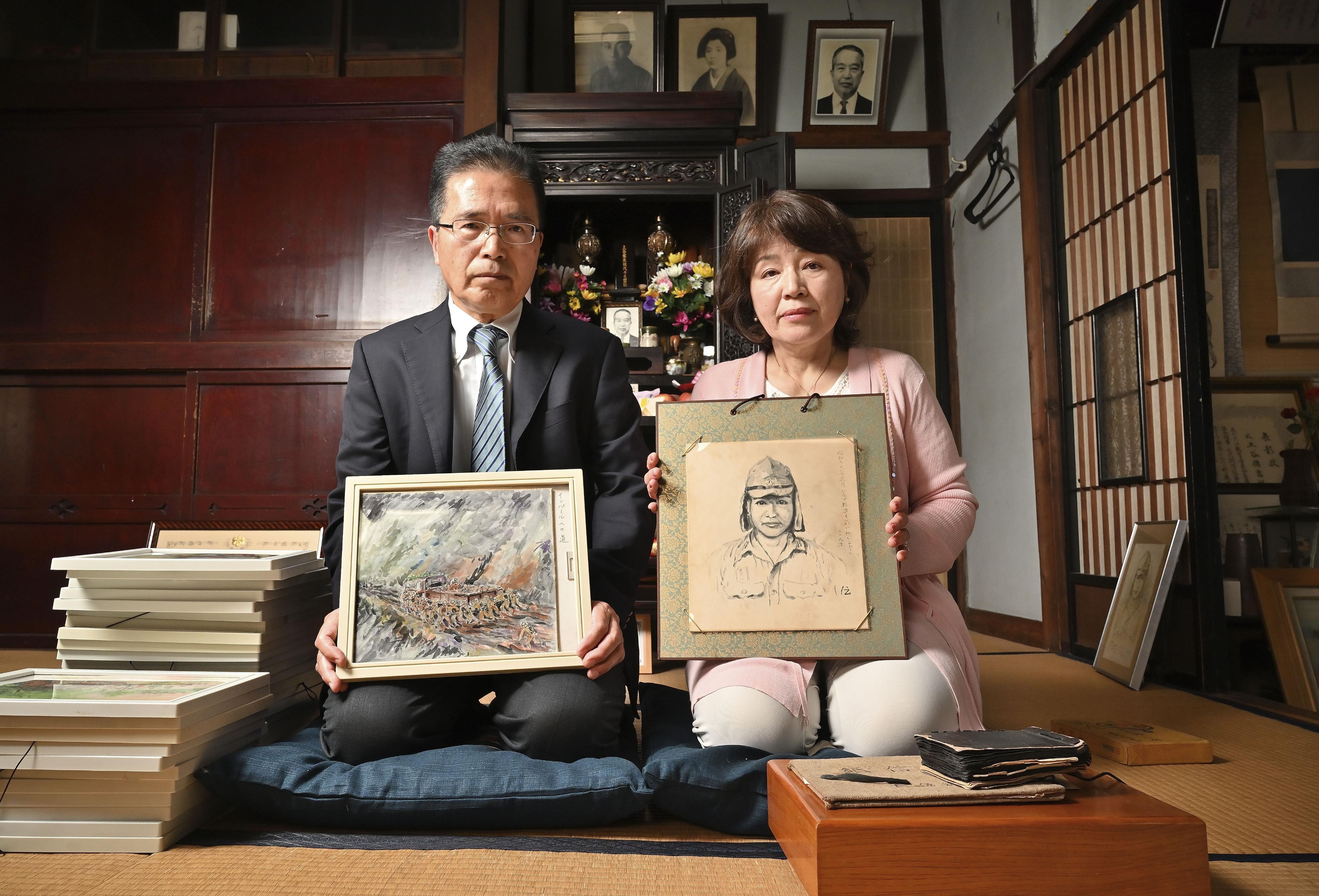 父土谷伝吉の自画像を持つ平岩真理と「インパール平和資料館」に寄贈の絵を手にする長男土谷仁志=静岡市