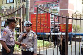 13日、インドネシア・メダンの警察本部の出入り口で、爆発後に警戒する警察官(アンタラ通信提供、ロイター=共同)