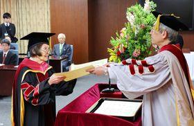 立命館大から博士の学位を授与された尾関清子さん(左)=24日午前、京都市
