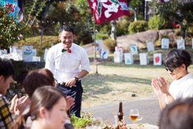1日限りの野外レストランに集まった客たちの前であいさつする横山太郎さん