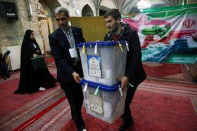 イラン国会選挙で投票締め切り後、投票箱を運ぶスタッフら=22日、テヘラン(WANA提供、ロイター=共同)