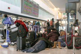 成田空港のロビーで寝袋に入り横になったり、座り込んだりする利用客ら=23日午前