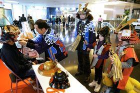 甲冑の試着を楽しむ家族連れ=18日、東京・羽田空港国際ターミナル