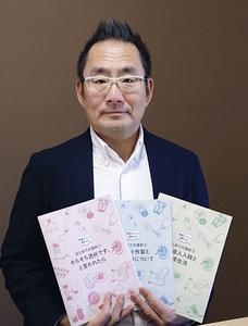 透析患者向けの生活ガイドブックの見本を示す宿野部武志さん