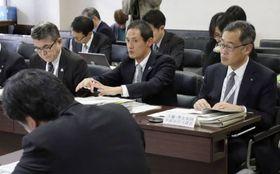 川崎市議会の委員会で、条例素案の修正点について説明する市の担当者(中央)ら