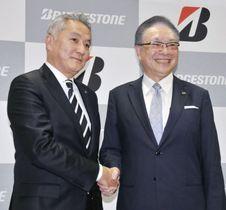記者会見で握手するCEOに就任する石橋秀一氏(左)と津谷正明氏=13日午後、東京都港区