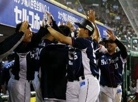 9回1死、逆転満塁本塁打を放ち、ベンチ前でナインとタッチを交わす西武・秋山(手前)