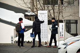 受験番号を確認し、試験場に向かう受験生ら=18日、青森市の青森大学