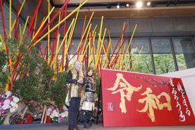 制作した生け花と書の前で写真に納まる華道家の假屋崎省吾さん(左)と書道家の青柳美扇さん=25日午後、東京都千代田