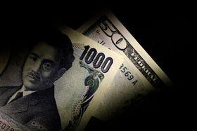 千円札と50米ドル札(ロイター=共同)