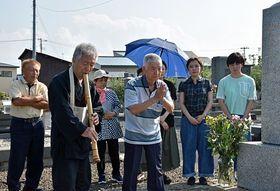 両親の墓前で追悼の尺八演奏をささげる中村興次さん(左から2人目)と手を合わせる興三郎さん(中)ら=板柳町三千石