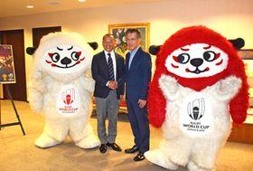 公式マスコットのレン(左)とジー(右)に囲まれて握手をする大会アンバサダーの広瀬佳司氏(中央左)と西日本新聞社の柴田建哉社長