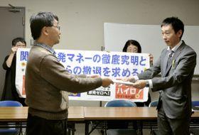 関西電力役員らの金品受領問題を受け、大阪市の担当者(右)に要望書を提出する反原発団体の代表者=12日午前、大阪市役所