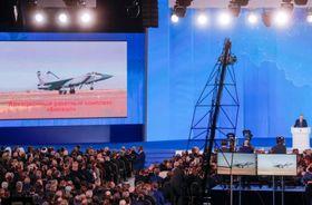 大型スクリーンで新型兵器を発表するロシアのプーチン大統領(右端)=3月1日、モスクワ(タス=共同)