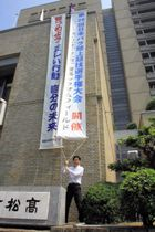 日本パラ陸上競技選手権大会の懸垂幕を設置する松下副市長=高松市役所