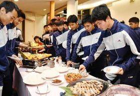 興味津々な様子で、トップチームの食事を皿に盛るサガン鳥栖U-15の選手たち=鳥栖市の花やしき