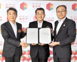 芳見所長(左)から通知書を受ける佐藤理事(中央)。右は高橋町長