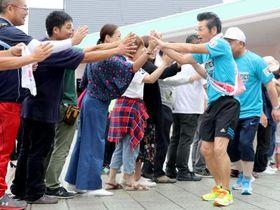 「みちのくマラソン」で、住民らとハイタッチしながら出発する間寛平さん(右)=12日、福島県富岡町